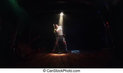 Scrubwoman in gloves sing on stage in concert microphone...