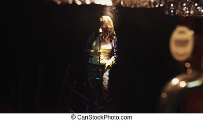 Scrubwoman in gloves sing on stage in vintage microphone under spotlight. Dance.