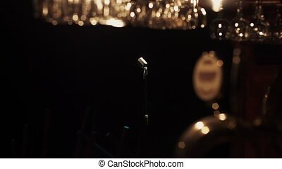 Bar stand of empty club. Vintage microphone stand on stage under spotlight.