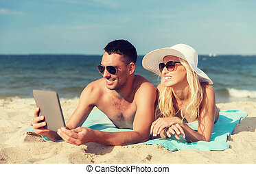 happy couple with tablet pc sunbathing on beach - love,...