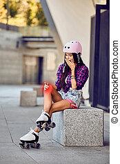 The girl on roller skates hurt knee in urban park
