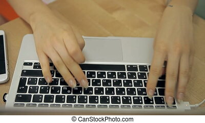 A woman is working on a laptop - Ladies hands are pushing...