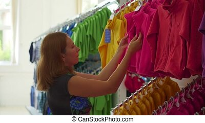 woman in the clothing store is considering clothes
