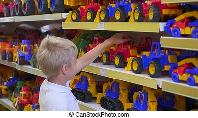 a child in a toy store looking at a car - the child in the...