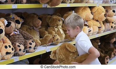 a child plays with a soft toy in the shop - a child plays...