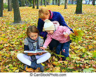 Mother with her daughters read a book in the park