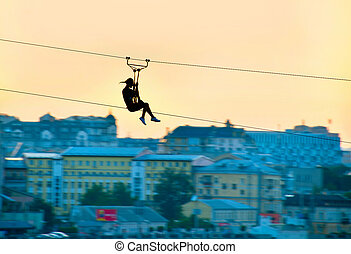 Urban ziplining - Silhouette of a woman on a zipline above...