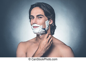 Morning shave. Handsome young shirtless man shaving and looking at camera while standing against grey background