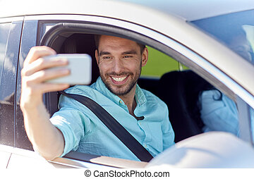 happy smiling man with smartphone driving in car - road...