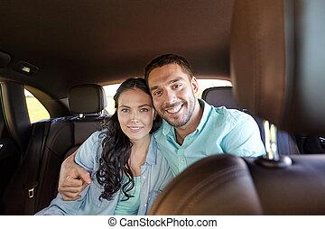 happy man and woman hugging in car - transport, road trip,...