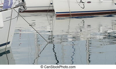 Slow Motion. White yachts in harbor, reflections in calm water, blue morning sky