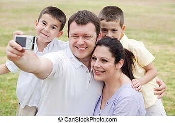 Cheerful family of five taking self portrait on natural...
