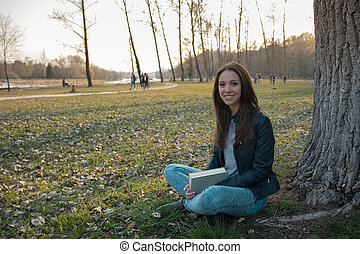 Woman relaxing at the park - Happy smiling woman relaxing at...