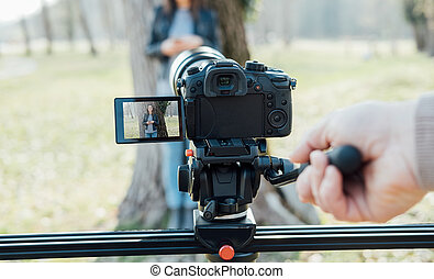 Video shooting at the park: video camera and operator hand...