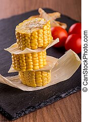 Stack of sweet corn portions on slate plate - Vertical photo...