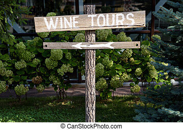 Wooden wine tour sign with arrow with green shrubs