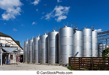 Photo of metal wine barrels at factory with blue sky