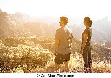 Young couple admiring the mountain view - Two young people...