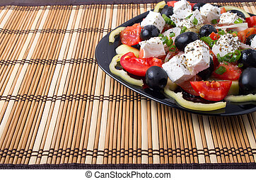 Side view of fresh vegetarian salad on a black square plate...