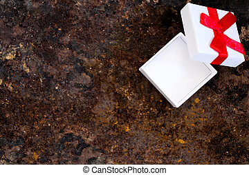 little gift box with red ribbon, rusty ground, copyspace