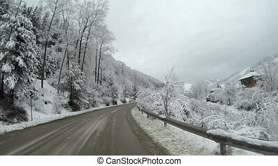 View of an empty road in the mountains during winter with...