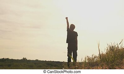 boy raises his hand up in a clearing superhero slow motion...