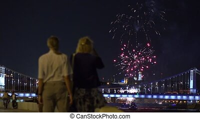People watching and making photoes of fireworks over bridge....