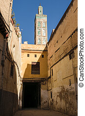 Alley and minaret of Mosque, Fes, Morocco - A typical small...