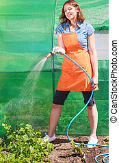 Woman watering the garden with hose - Gardening. Woman in...