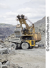 Opencast mining - Excavator loading the ore to the truck on...