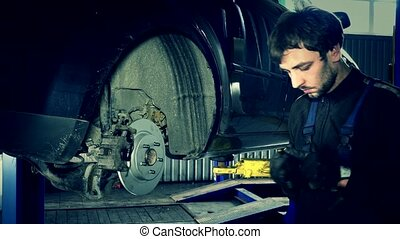 car specialist at work. man work on brake system. color...