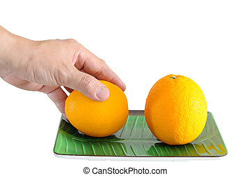 Man hand picking one oranges on plate isolated with clipping path