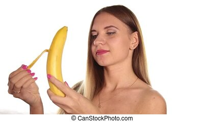 naked young woman wears red lipstick and has her hair down, and brushed, peeling and eating a big banana. healthy food - strong teeth concept. On a white background