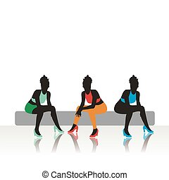 The beautiful girls sits on a sofa
