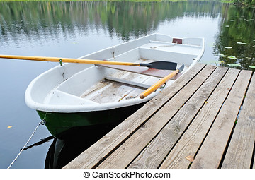 rowing boat at the pier - empty rowing boat near a wooden...