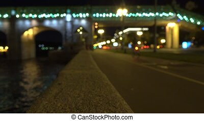 Blurred cyclist on urban embankment at night. 4K bokeh clip