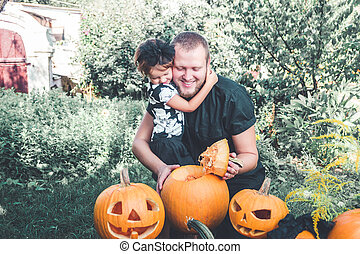 Halloween Daughter hugging father Man cuts a lid from...