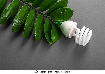 LED lamp with green leaf, ECO energy concept, close up. Light bulb on grey background. Saving  and Ecological Environment. Copy space.