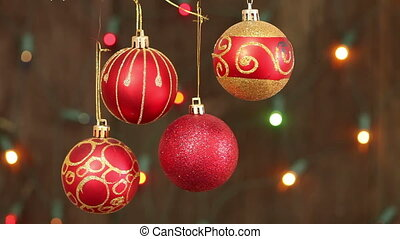 red Christmas balls hanging on strings. Flashing a garland...