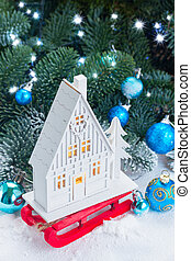 White christmas house on red sledge with blue decorations in...
