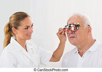 Female Optometrist Checking Patient's Vision With Trial Frame