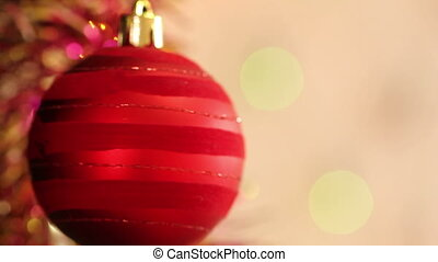 red ball on the Christmas tree with blinking garlands in...