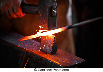 Blacksmith at work - The hands of a blacksmith at work in...