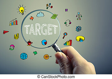 Target Business Concept - Hand holding magnifying glass is...