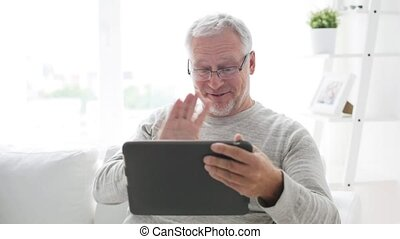 senior man having video call on tablet pc at home -...