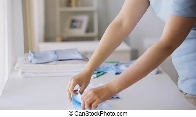 pregnant woman folding baby boys clothes at home 26 -...