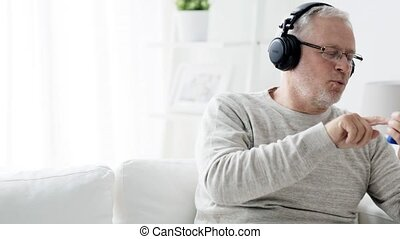 happy senior man with smartphone and headphones 93 -...