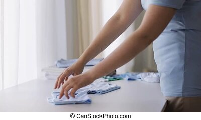 pregnant woman folding baby boys clothes at home 18 -...