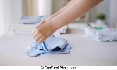 woman hands folding baby boys clothes at home 22 -...