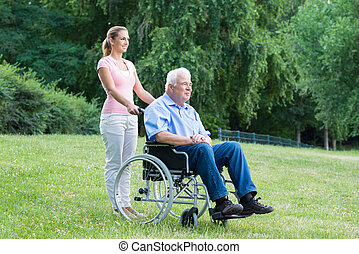 Woman With Her Disabled Father On Wheelchair - Smiling Young...